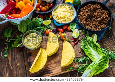 Mexican tacos with ingredients on wooden table. Overhead view, traditional street food. - stock photo
