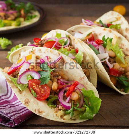 Mexican tacos with meat, beans and salsa - stock photo