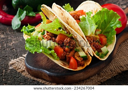 Mexican tacos with meat, vegetables and cheese - stock photo
