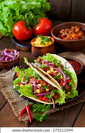 Mexican tacos with meat, vegetables and red onion - stock photo