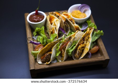 Mexican Tortilla with meat, beef and stewed vegetables and spicy sauce on a wooden tray - stock photo