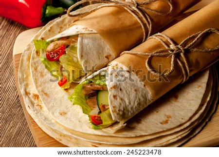 Mexican tortilla wrap with meat and vegetables on wood table - stock photo