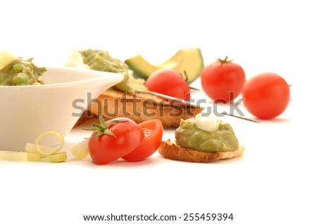 Mexican typical food - Fresh guacamole on whole grain rusk and tomatoes isolated on white background - stock photo