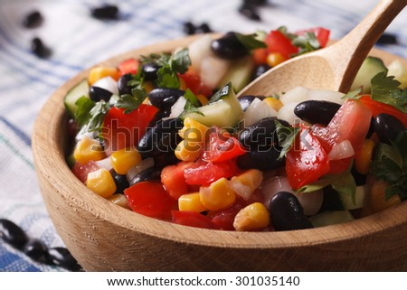 Mexican vegetable salad with black beans, avocado, corn and tomatoes macro in a wooden plate. horizontal