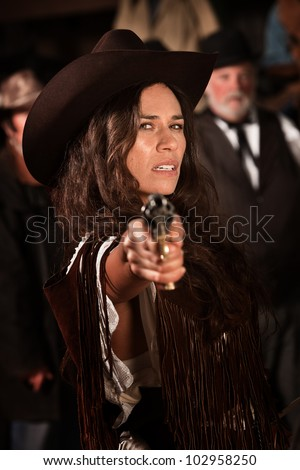 Mexican woman in old west style clothes points a revolver - stock photo