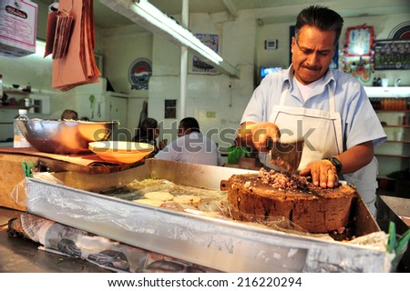MEXICO CITY - FEB 23 2010:Mexican butcher cuts meat.Most of the Mexican dish recipes were developed by the Mayas and Aztecs. - stock photo