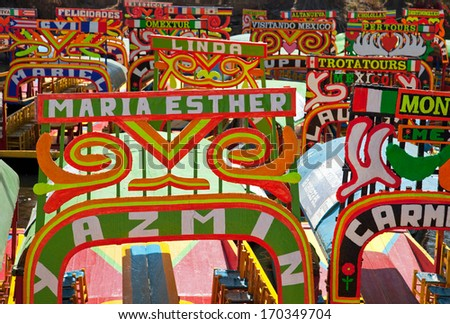 MEXICO CITY - MARCH 17: Colorful boats parked on a canal in Xochimilco Floating Gardens on March 17, 2011 in Mexico City, Mexico. Hiring these boats for a canal ride is a popular activity by tourists. - stock photo