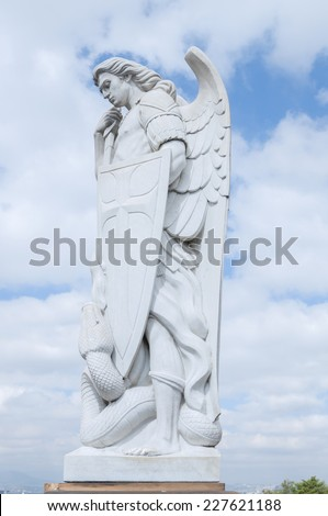 MEXICO CITY, MEXICO - OCTOBER 23, 2014: A beautiful tall marble statue of the Archangel Michael stands on top of Tepeyac Hill under a cloudy sky near the Basilica of Guadalupe in Mexico City - stock photo