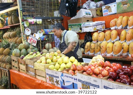 MEXICO CITY - SEPTEMBER 3 : Fruit stall vendor tends his produce in the Merced Market on September 4, 2008 in Mexico City. - stock photo