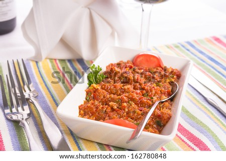 Meze, diced tomatoes with parsley, walnuts and hot red peppers seasoned with lemon juice served on a colorful  place mat - stock photo