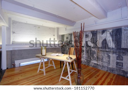Mezzanine office in reconstructed modern living room. View of old concrete wall, and white painted ceiling beams. Furnished with simple desk and chair. Decorated with dry branches in a glass vase - stock photo