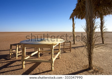 MHAMID, MOROCCO, NOVEMBER 18: View of desert with old wooden chairs and table next to a sun shelter with clear blue sky. Morocco 2010.