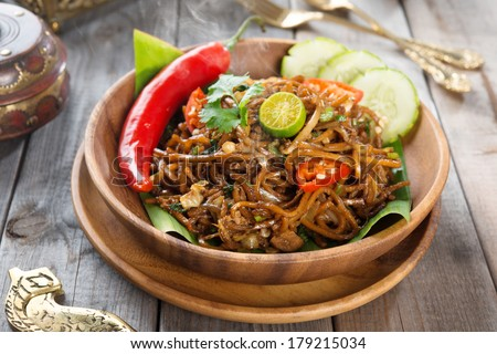 Mi goreng or mee goreng mamak, Indonesian and Malaysian cuisine, spicy fried noodles with wooden dining table setting. Fresh hot with steamed smoke. - stock photo