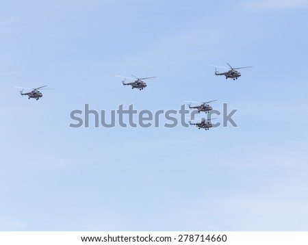Mi-8 helicopters flying formation against a blue sky - stock photo