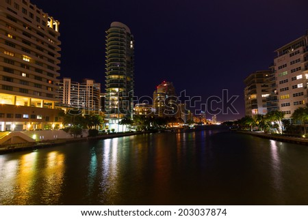 Miami Beach city landscape at night. Modern buildings along the waterfront with colorful reflections.
