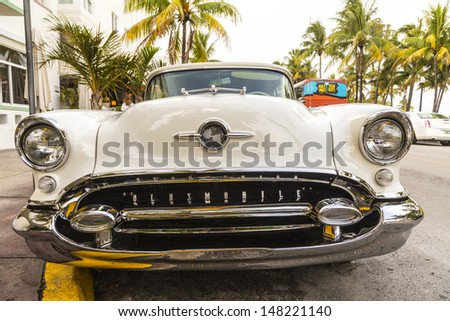 MIAMI BEACH, FL - JULY 30: classic Oldsmobile with chrome radiator grill parked in front of the restaurant in Hotel Avalon in Miami Beach, Florida. on July 30, 2013. - stock photo