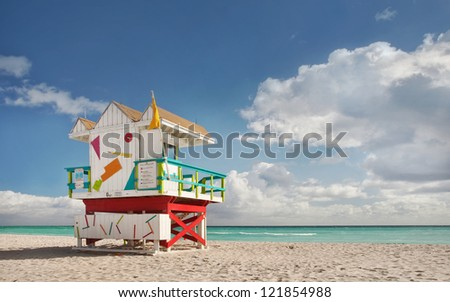 Miami Beach Florida, lifeguard house in typical colorful Art Deco style on a sunny summer day, with blue sky, and Atlantic Ocean in the background. World famous travel location. - stock photo