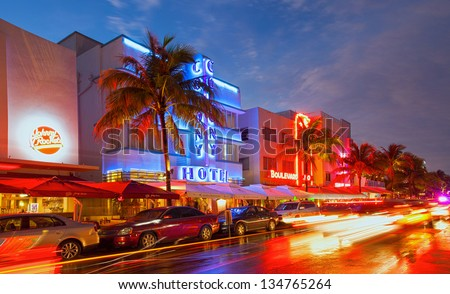 MIAMI BEACH, FLORIDA, USA-APRIL 5: Illuminated hotels and restaurants at sunset on Ocean Drive on April 5, 2013, world famous destination for nightlife, beautiful weather and pristine beaches - stock photo