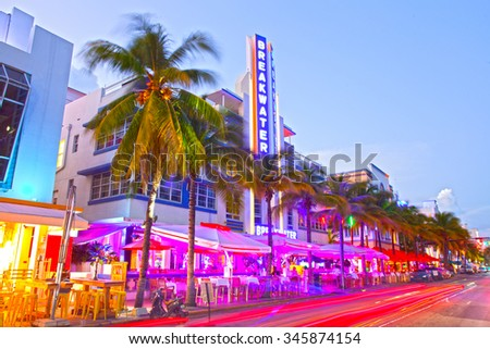 Miami Beach, Florida USA-November 10, 2015: Moving traffic, Illuminated hotels and restaurants at sunset on Ocean Drive, world famous destination for nightlife, beautiful weather, Art Deco and beaches - stock photo