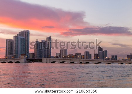 Miami city skyline panorama at twilight with urban skyscrapers, marina and bridge
