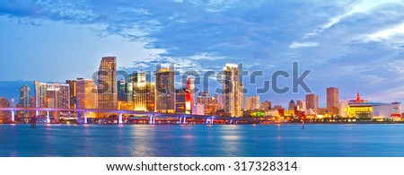 Miami Florida at sunset, cityscape of modern downtown buildings illuminated with reflections in the waters of Biscayne BAy - stock photo