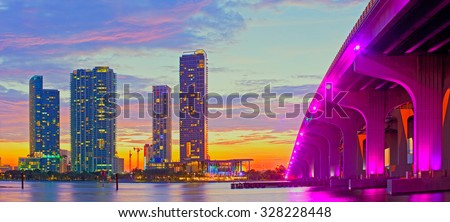 Miami Florida at sunset, colorful skyline of illuminated buildings and Macarthur causeway bridge - stock photo