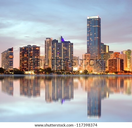 Miami Florida, cityscape of illuminated downtown buildings at sunset with reflections in the water of Biscayne Bay. Panoramic skyline of the World famous travel location - stock photo