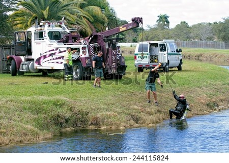 MIAMI, FLORIDA - DECEMBER 14, 2014: A Miami-Dade County Sheriff Department's diver is hoisted out of a canal in a residential neighborhood after investigating a submerged object. - stock photo
