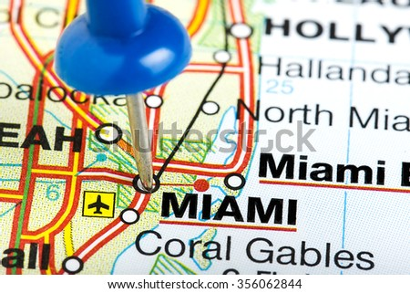 Miami Florida highlighted with blue push pin on atlas or map - stock photo
