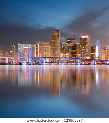 Miami Florida illuminated downtown buildings and bridge at sunset with reflections in the water of Biscayne Bay. Panoramic skyline of the World famous travel location.