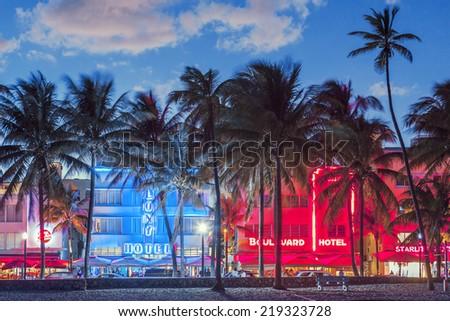 MIAMI, FLORIDA - JANUARY 24, 2014: Palm trees line Ocean Drive. The road is the main thoroughfare through South Beach.  - stock photo