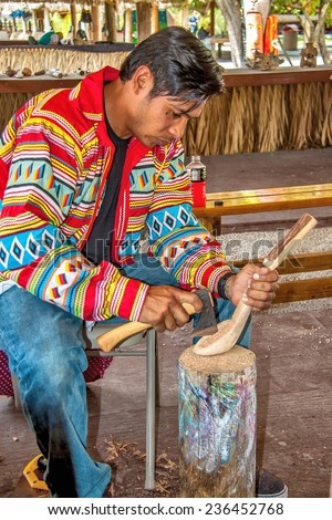 MIAMI, FLORIDA - May 25, 2014: Miccosukee Indian carving wooden cooking utensils. The Miccosukee Tribe is a federally recognized Indian Tribe residing in Florida Everglades just west of Miami.