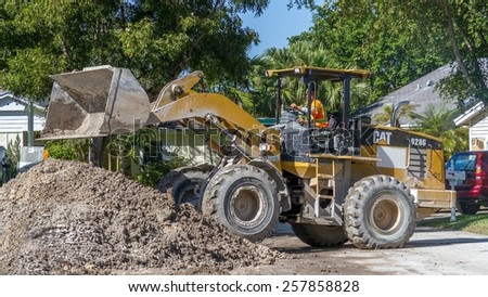 Miami, Florida - November 07, 2014:  A front loader working on a construction site in a residential neighborhood, improving the draining system for the wet rainy season - stock photo