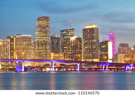 Miami Florida sunset over downtown business and luxury residential buildings, hotels and illuminated bridge over Biscayne Bay.  Cityscape of World famous travel destination. - stock photo