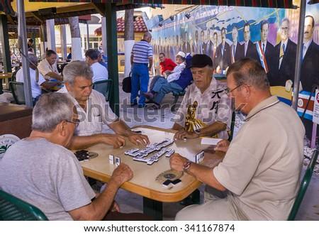 MIAMI, FLORIDA, USA - MAY 2004: Elderly Cuban men play dominoes at Gomez Park, on Calle Ocho (8th Street), the heart of Little Havana. - stock photo