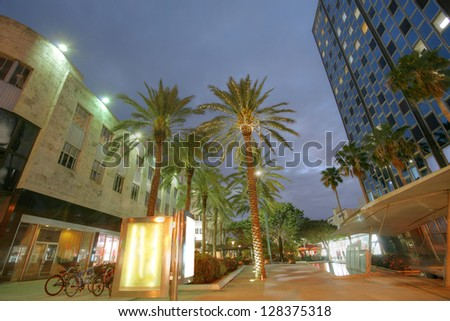 MIAMI - JAN 31: Tourists enjoy sights and buildings of Lincoln Road in sunset, January 31, 2013 in Miami. Once open to vehicular traffic, the street now hosts a pedestrian row of shops & restaurants. - stock photo