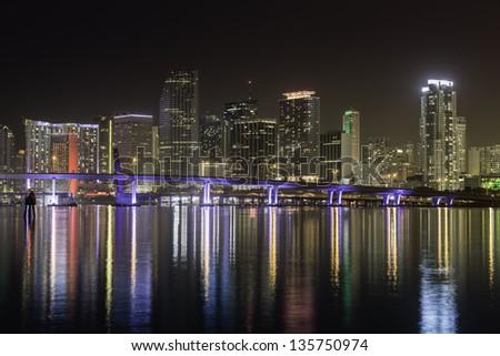 Miami skyline by night with illuminated  port bridge - stock photo