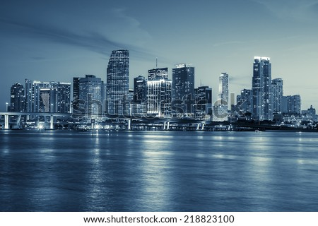 Miami skyline panorama at dusk with urban skyscrapers and bridge over sea with reflection  - stock photo