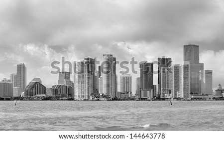 Miami skyline panorama in black and white in the day with urban skyscrapers and cloudy sky over sea - stock photo