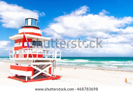 Miami, South Beach, Florida, lifeguard house in a typical colorful Art Deco style on cloudy day with blue sky and Atlantic Ocean in background, world famous travel location
