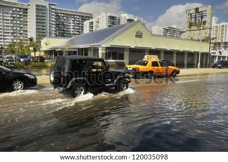 MIAMI - SOUTH BEACH - FLORIDA, OCTOBER 28: Car cross Miami South beach Lenox Ave flood aftermath of Hurricane Sandy on october 28 2012 in Miami South Beach. - stock photo