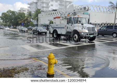 MIAMI - SOUTH BEACH - FLORIDA, OCTOBER 28:  Electricity truck cross Miami South beach Lenox Ave flood aftermath of Hurricane Sandy on october 28 2012 in Miami South Beach. - stock photo
