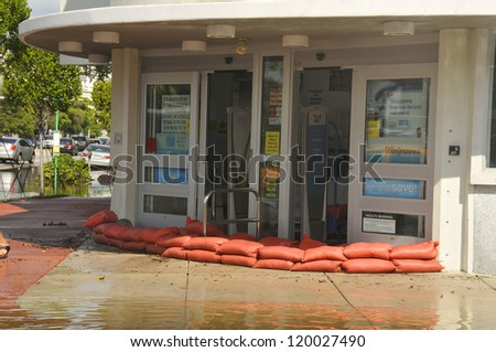 MIAMI - SOUTH BEACH - FLORIDA, OCTOBER 28: People put sand bags in front door of a store in Miami South beach Lenox Ave flood aftermath of Hurricane Sandy on october 28 2012 in Miami South Beach. - stock photo