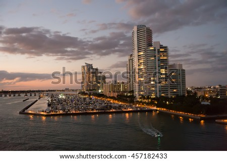 miami, south beach : modern buildings near water at bay with many boats at sunset and illuminating lights on cloudy evening sky background, night scene