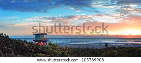 Miami South Beach sunrise panorama with lifeguard tower and coastline with colorful cloud and blue sky. - stock photo