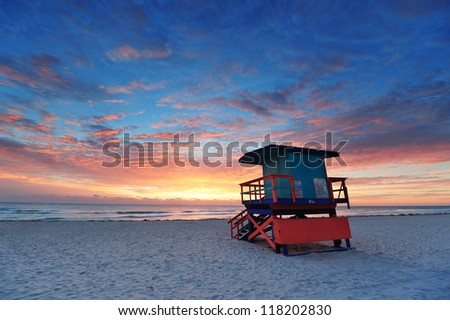 Miami South Beach sunrise with lifeguard tower and coastline with colorful cloud and blue sky. - stock photo
