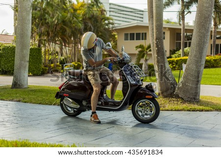 MIAMI, USA - APRIL 30, 2016: Young man on a Piaggio Vespa GTV 300ie on APRIL 30, 2016 in Miami, USA.