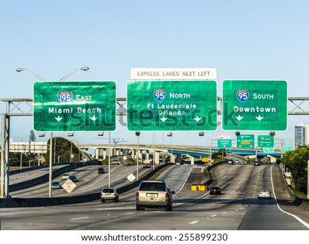 MIAMI, USA - AUG 27, 2014: driving the Miami Highway from the airport direction East in Miami, USA. Sunpass lane on left hand side is for toll only. - stock photo