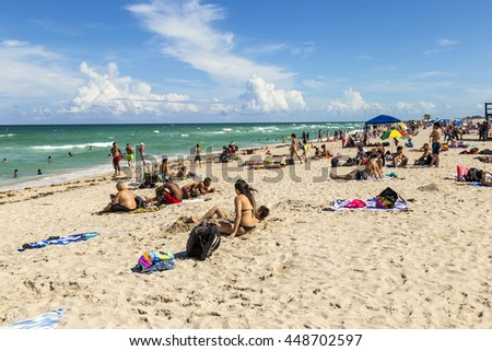 MIAMI, USA - AUG 1, 2013: people enjoy the hot summer day at south beach in Miami, USA. South beach is the famous beach at art deco district neaqr ocean drive street.