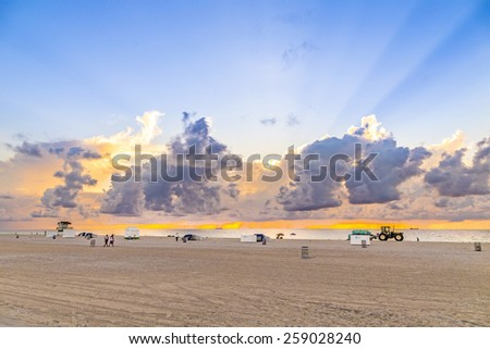 MIAMI, USA - AUG 7, 2013: people in late afternoon walk along south beach and enjoy the sunset in Miami, USA. South beach is famous for spectacular sunsets. - stock photo